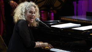 Carole King sjunger och spelar piano.