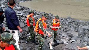 Räddningsarbetare letar efter överlevande bland stenblock i byn Xinmo, Sichuanprovinsen i Kina, efter jordskredet 24.6.2017