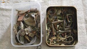 Två lådor fyllda med olika metallföremål, till exempel spännen från bälten