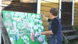 Kvinna rör med pensel på tavla som är grön och täckt med ritade träd.
