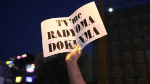 """En demonstrant håller upp en text med """"rör inte min radio och tv"""" då 20 rado och tv-stationer stängdes i Turkiet hösten 2016"""