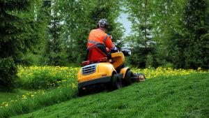 Person i granna skyddskläder klipper gräset med åkgräsklippare.