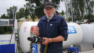 Göran Wikström vid Sommaröstrand håller i sugslangen för tömning av septiktank i båt.