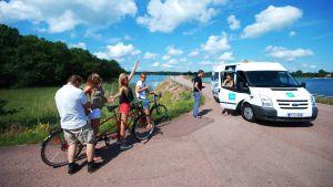 Forografen justerar en mikrofon i samband med att vi filmar cykling på Åland till En svensk sommar i Finland.
