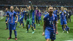 Isländska fotbollspelare i blå-röd-vita tröjor vrålar av glädje pp fotbollstadium Stade de Nice efter att de vunnit matchen mot England 2-1.