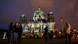 Turister ser på ljusshow i Berlin