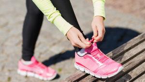 En kvinna knyter skosnöret på sina rosa löparskor.