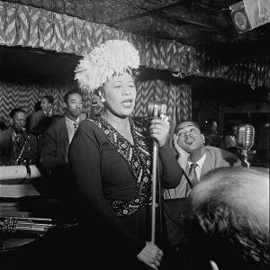 Ella Fitzgerald laulaa, taustalla Dizzy Gillespie katselee ihailevasti. Arkistokuva, tv-dokumentista Ella Fitzgerald, jazzin kuningatar (2017).