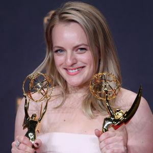 Elisabeth Moss håller upp två Emmystatyetter.