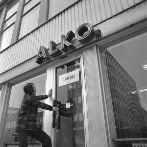 """Alkon lakko 1972. Alkon lakko alkoi 24.04.1972 ja päättyi kesäkuun alussa. Alko Oy, myymälä. Ovessa lappu """"Lakko"""". Mies yrittää avata myymälän ovea (lavastettu kuva)."""