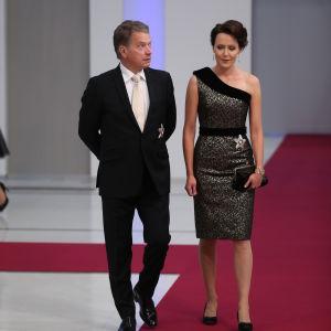 Man och kvinna skrider in på röd matta