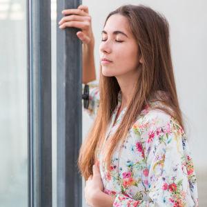 Kvinna andas vid öppet fönster.
