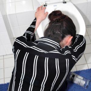 En kvinna böjer sig över en toalettskål.