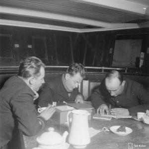 Sähkösanoma muutetaan salakirjoitukseksi. Kolme miestä pöydän äärellä. Paikka: Itämeri. Laivassa?