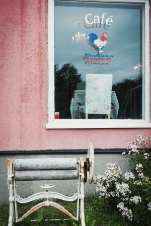 """Vanha käsikäyttöinen mankeli pinkiksi maalatun talon edessä. Ikkunassa teksti """"Ranskalainen kyläkauppa""""."""
