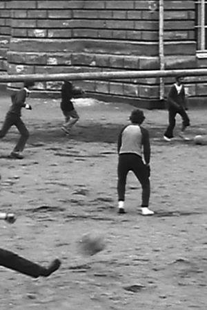 Folk som spelar fotboll på en sandplan.