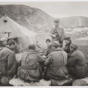Venäläsiä sotavankeja nuotionŧmpärillä, taustalla teltta, tunturinrinne  ja rakennuksia.