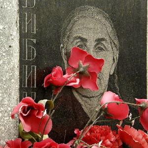 Hautakivi ja punaisia kukkia