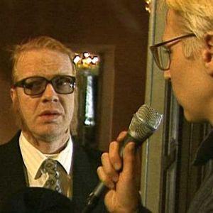 """Kummelin pääministeri (Heikki Silvennoinen)ja tämän erikoisavustaja Pentti """"Pena"""" Hietanen (Timo Kahilainen) haastattelussa pakoilaisista."""