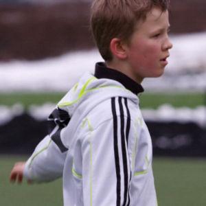 Poika pelaa jalkapalloa Helsingin Stadionilla