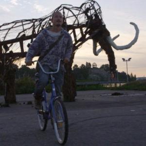 Mies pyöräilee mammuttiteoksen edessä.