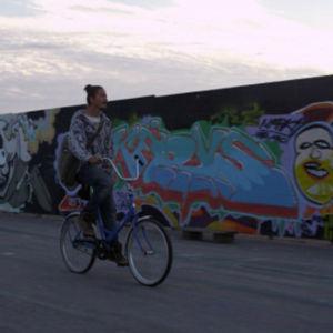 Mies pyöräilee graffitiseinän edessä.