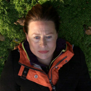 Nainen makaa sammaleella metsässä