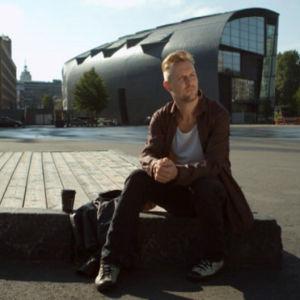 Mies istuu kansalaistorilla Helsingissä.