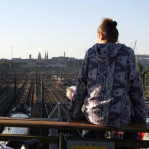 Mies istuu junaratan ylittävällä sillalla.