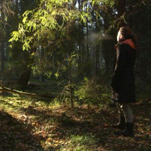 Nainen seisoo metsässä.