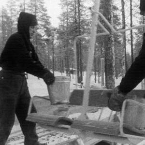 Työmiehet kuljettavat soraa hiihtohissillä.