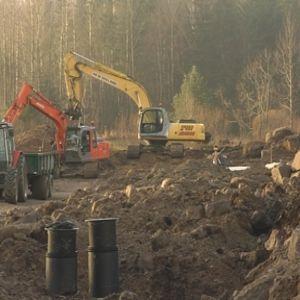 Grävmaskin i skogsmiljö.