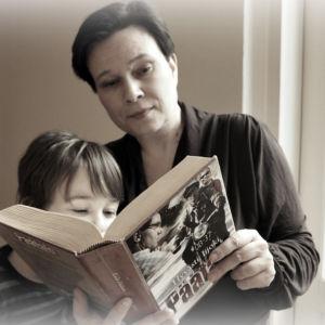 Kirjabloggaaja Minna Vuo-Cho lukee Kalle Päätaloa lapsensa kanssa.