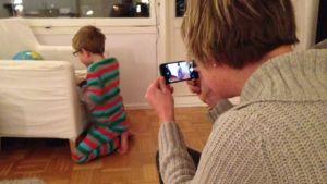 En mamma fotograferar sitt barn med mobil