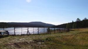 joen/järvenrantaniittyä, puinen aita, puinen vene kumollaan