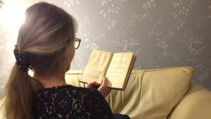 Nainen lukee kirjaa tohvelit vieressään