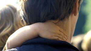 Ett barns arm om pappas hals