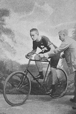 Arvid Lind valokuvaamossa polkupyörän selässä. Suomen Kuvalehti v. 1894.