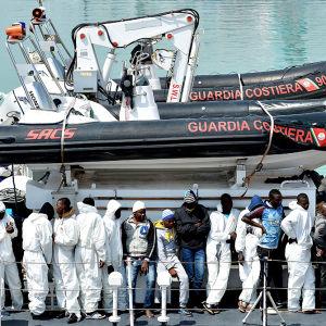 Flyktingar anländer till hamnen i Catania efter den tragiska båtolyckan där minst 700 personer dog.