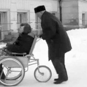 Vanha mies työntää nuorempaa pyörätuolissa
