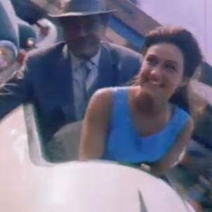 Tummahiuksinen nuori nainen ja vanhempi mies istuvat huvipuiston laitteessa