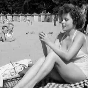 Nainen syö tomaattia viltin päällä hiekkarannalla ohjelmassa Aurinko ja meri (1957)