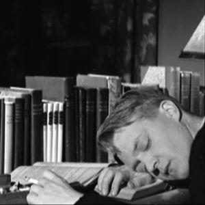 Opiskelijapoika nukkuu kirjan ääressä tupakka kädessä.