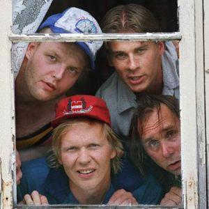 Peräkamaripojat-sarjan neljän miesnäyttelijää kurkistaa ikkunasta