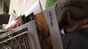Lehtiteline etualalla, lehden lukija takana