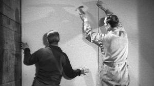 Miehet asentavat kuitulevyä seinään