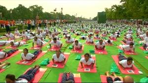 Tiotusentals människor yogar i Delhi
