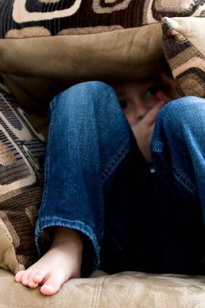 Pieni poika on piiloutunut tyynyjen alle