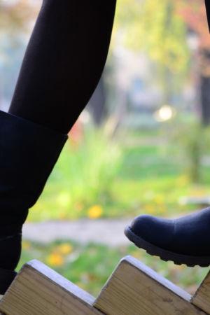 Mustat kengät aidalla.