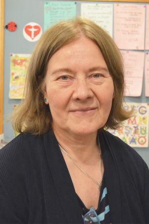En kvinna sitter framför en vägg med handskrivna och -ritade lappar.